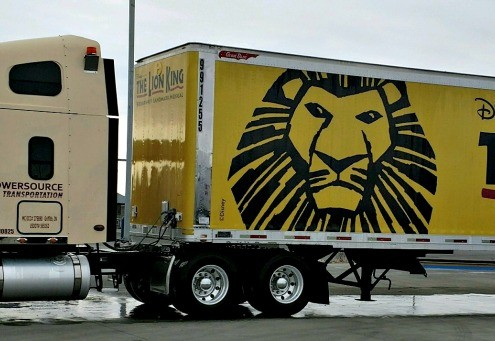 Powersource truck hauling Lion King broadway show trailer