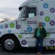 Powersource driver owner-operator Jeanne Ochland standing in front of her truck, decorated in daisies