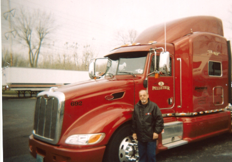 Powersource driver owner-operator Alan Pelletier standing in front of his truck.