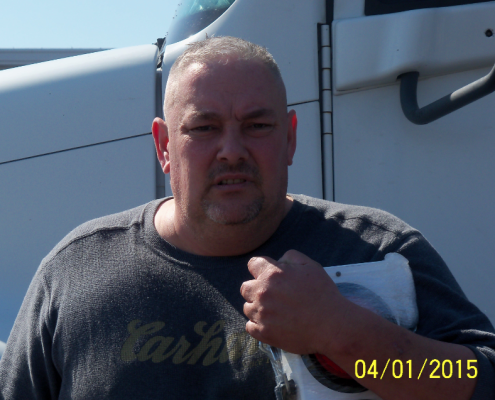 Powersource driver owner-operator Gary Petrie standing in front of his truck, close-up