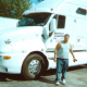 Powersource driver owner-operator Dwayne Larson standing in front of his truck