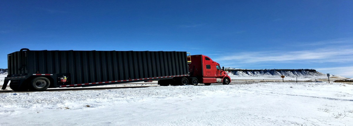 Powersource truck hauling over-dimensional container trailer on snowy terrain