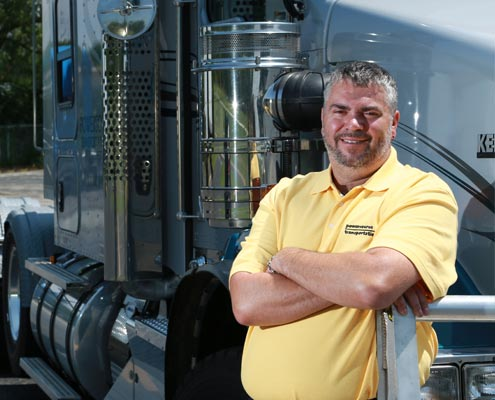 Powersource driver owner-operator Gabe Gelle standing in front of his truck