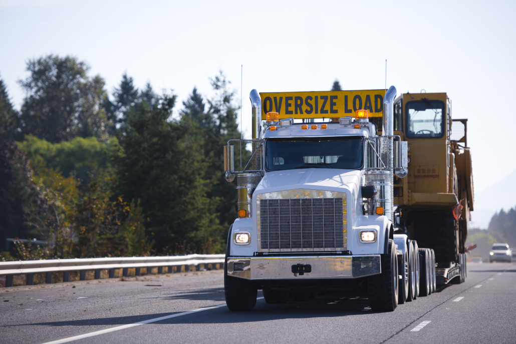 Big rig semi truck with oversize load sign and step down trailer carry and transporting digger