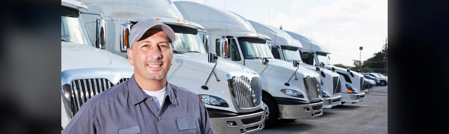 Truck Driver in Front of Row of White Trucks